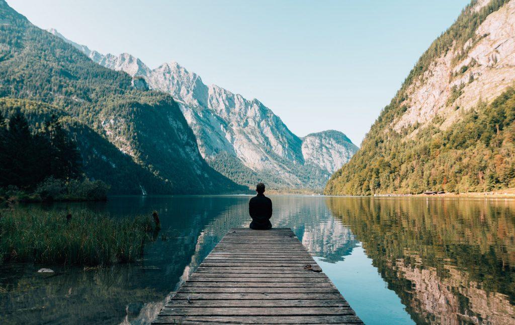 Pessoa meditando na beira de um lago