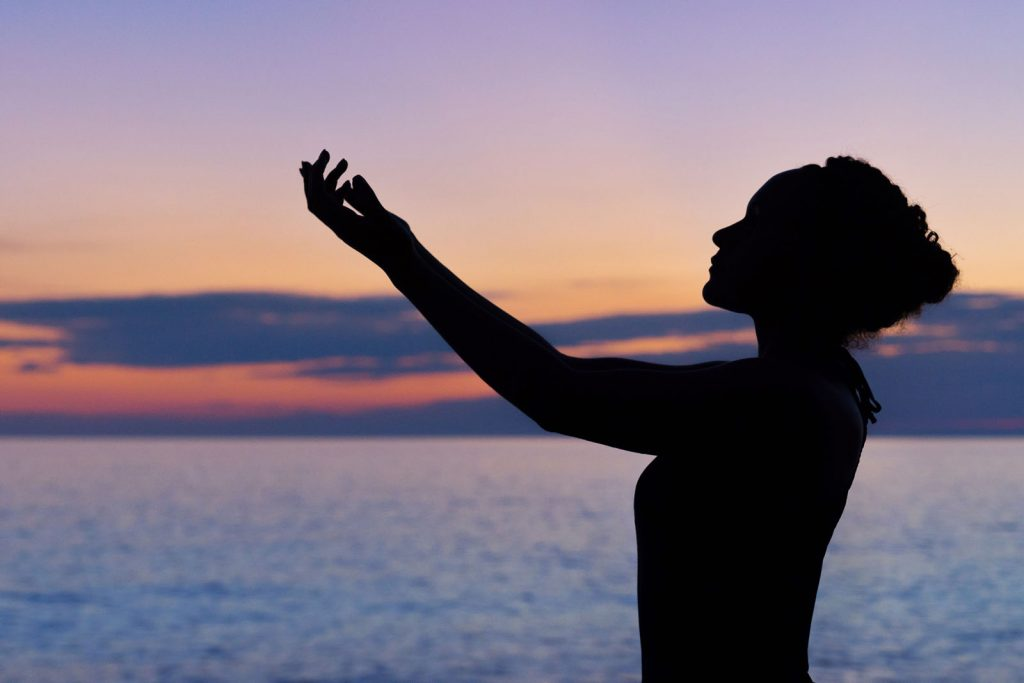 Mulher meditando em frente ao mar
